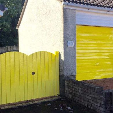 A garage door and fence that has been decorated by our team